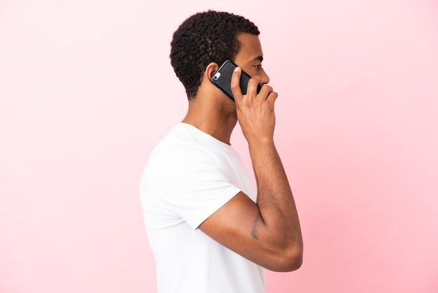 Homem afro-americano bonito em fundo rosa isolado, conversando com alguém ao telefone celular