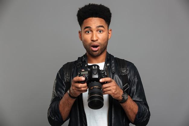 Homem afro-americano bonito espantado na jaqueta de couro, segurando a câmera digital