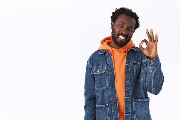 Homem afro-americano bonito, estiloso e descolado, barbudo, com capuz laranja e jaqueta jeans, mostrando sua permissão ou julgamento