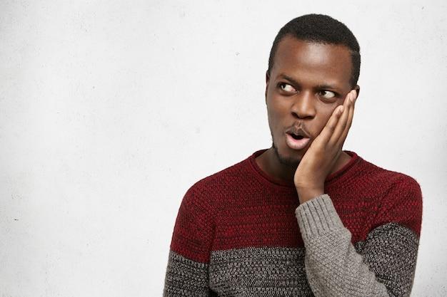 Homem afro-americano bonito jovem chocado ou surpreso exclamando com espanto, mantendo a mão na bochecha