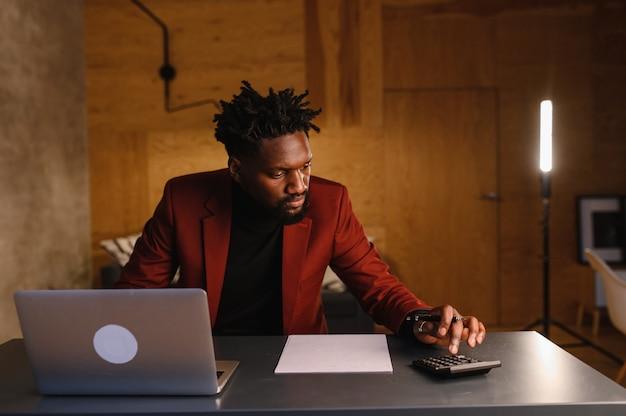 Homem afro-americano bonito negro trabalhando no computador portátil enquanto está sentado atrás da mesa na aconchegante sala de estar. freelancer, trabalhando em casa.