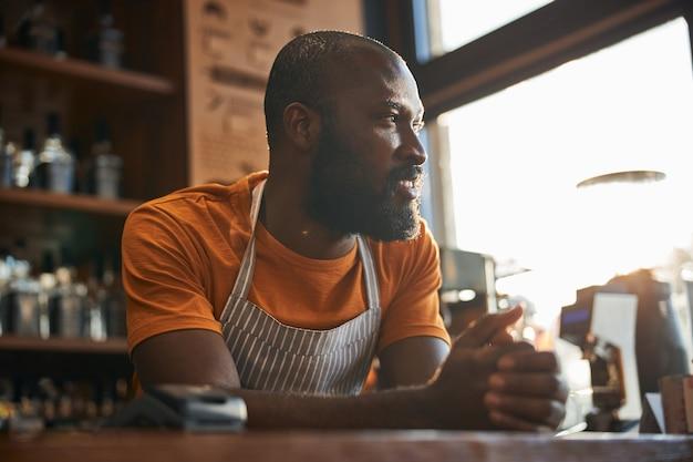 Homem afro-americano bonito parado no balcão do bar