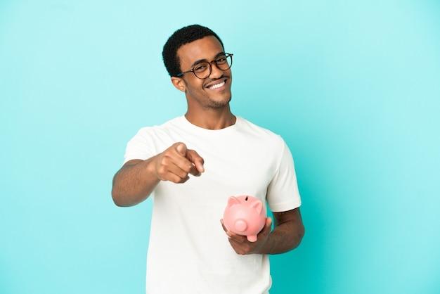 Homem afro-americano bonito segurando um cofrinho sobre um fundo azul isolado, apontando para a frente com uma expressão feliz