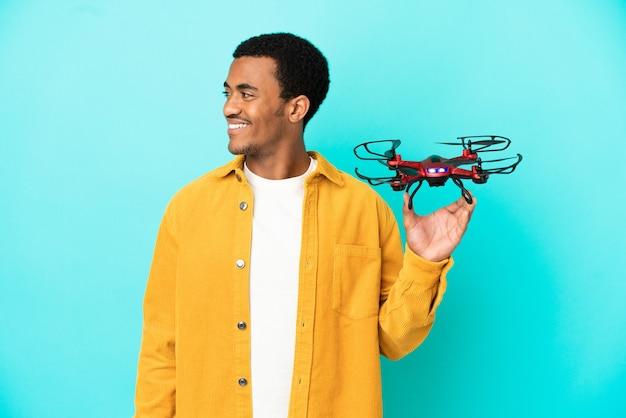 Homem afro-americano bonito segurando um drone sobre um fundo azul isolado, olhando de lado