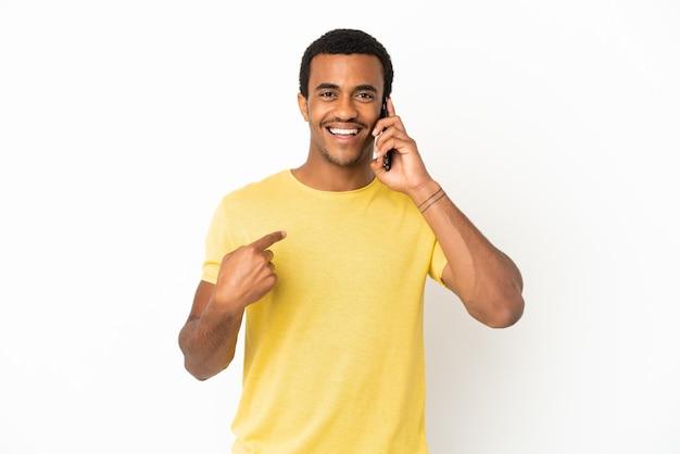 Homem afro-americano bonito usando telefone celular sobre fundo branco isolado e fazendo um gesto de polegar para cima