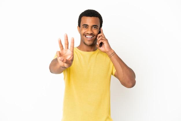 Homem afro-americano bonito usando telefone celular sobre fundo branco isolado feliz e contando três com os dedos