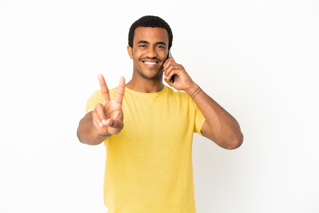 Homem afro-americano bonito usando telefone celular sobre fundo branco isolado, sorrindo e mostrando sinal de vitória