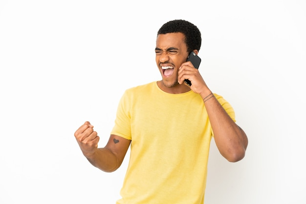 Homem afro-americano bonito usando telefone celular sobre um fundo branco isolado, comemorando uma vitória