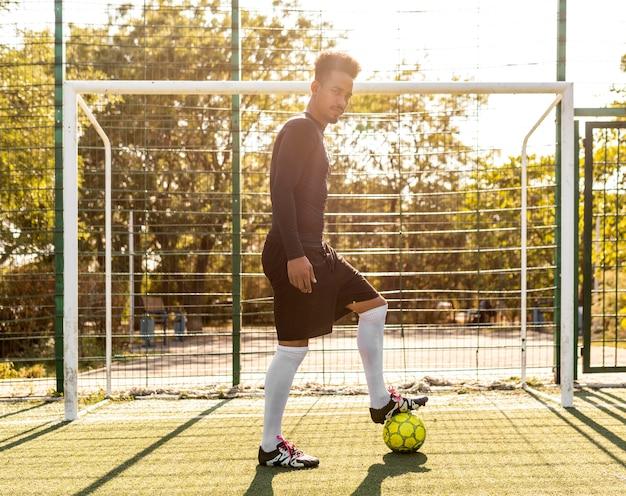 Homem afro-americano brincando com uma bola de futebol lá fora