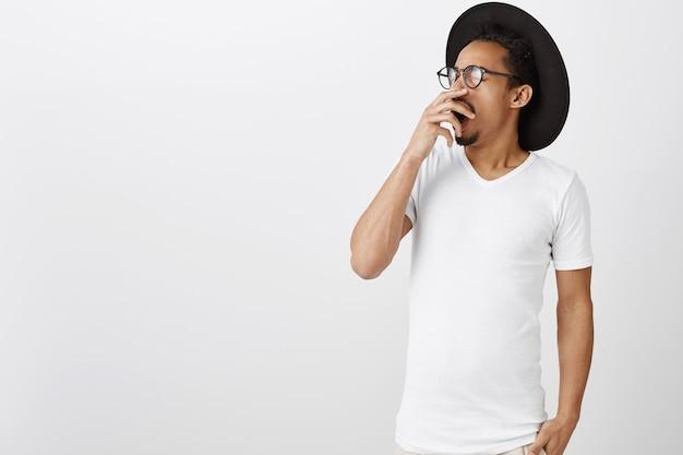 Homem afro-americano cansado ou com sono em uma camiseta casual bocejando, cobrir a boca aberta com a mão, sentindo-se exausto