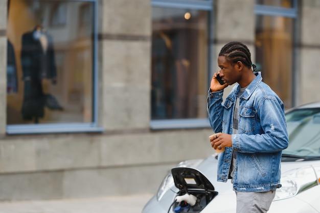 Homem afro-americano carregando seu carro elétrico.