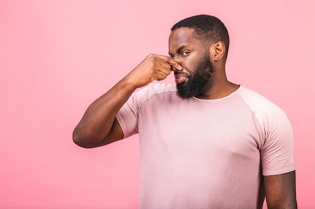 Homem afro-americano cheirando algo fedorento e nojento,