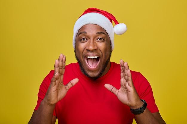 Homem afro-americano chocado com camiseta e chapéu de natal gritando com um gesto de mão para seu mou