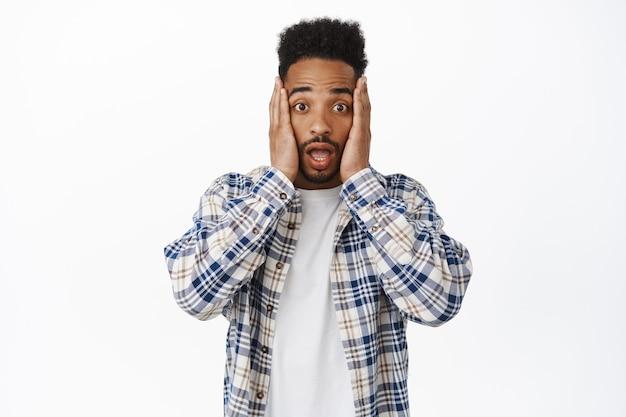 Homem afro-americano chocado e preocupado, de mãos dadas no rosto de bochechas, suspiro e olha nervosamente, ouve notícias chocantes, de pé no branco. copie o espaço