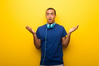Homem afro-americano com a t-shirt azul no fundo amarelo que tem dúvidas