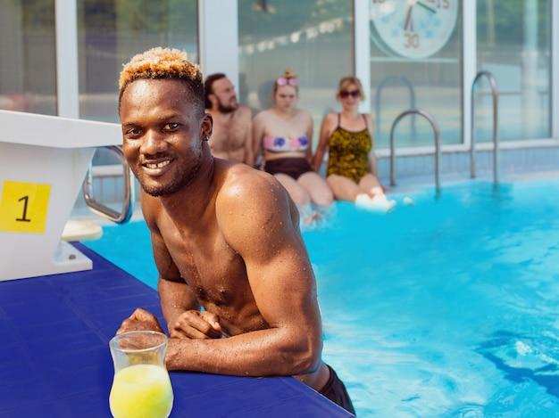 Homem afro-americano com amigos caucenses na piscina férias de verão e conceito de esporte