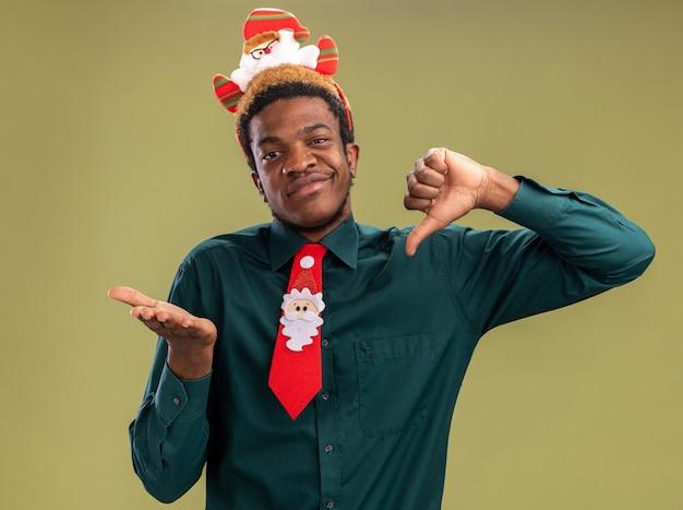 Homem afro-americano com aro de papai noel engraçado e gravata vermelha olhando para a câmera, olhando para a câmera confuso mostrando polegares para cima e para baixo em pé sobre um fundo verde