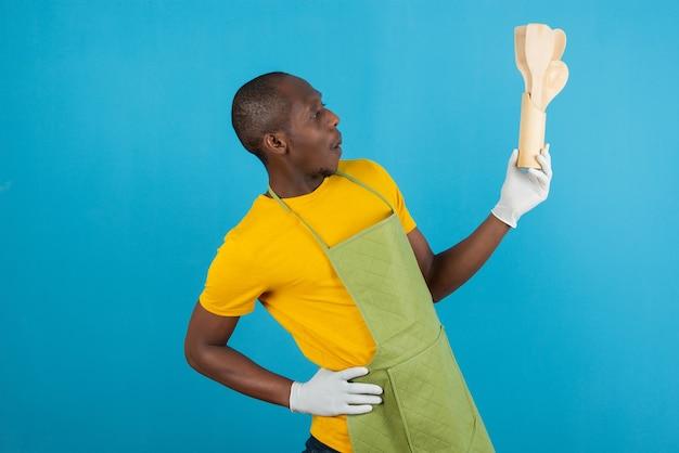 Homem afro-americano com avental verde segurando ferramentas de madeira de cozinha na parede azul