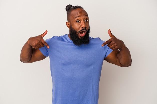Homem afro-americano com barba isolada em fundo rosa aponta para baixo com os dedos, sentimento positivo.