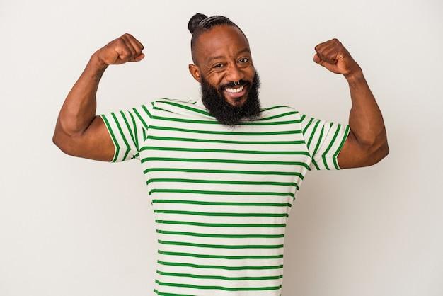 Homem afro-americano com barba isolada em fundo rosa, mostrando força gesto com os braços, símbolo do poder feminino