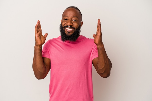 Homem afro-americano com barba isolada em fundo rosa ri alto, mantendo a mão no peito.