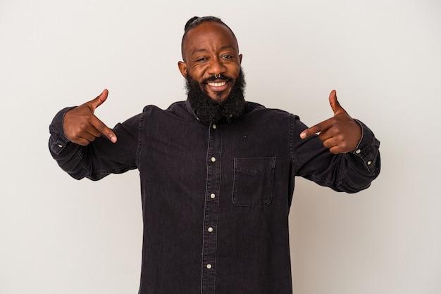 Homem afro-americano com barba isolada na parede rosa aponta para baixo com os dedos, sentimento positivo.