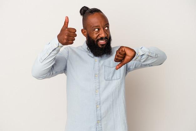 Homem afro-americano com barba isolada na parede rosa mostrando os polegares para cima e para baixo, é difícil escolher o conceito