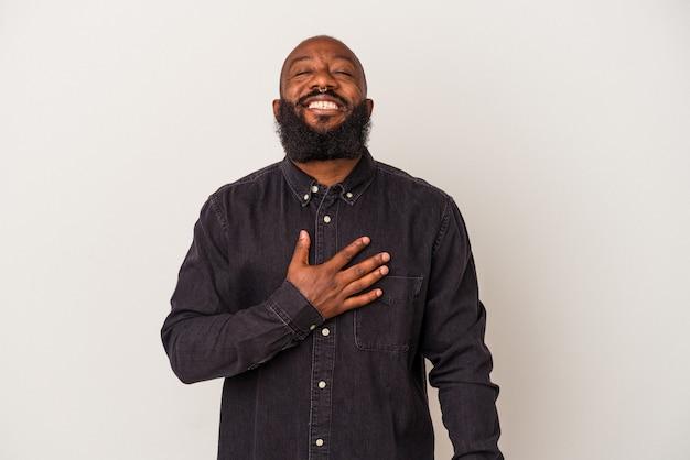 Homem afro-americano com barba isolada na parede rosa ri alto, mantendo a mão no peito.