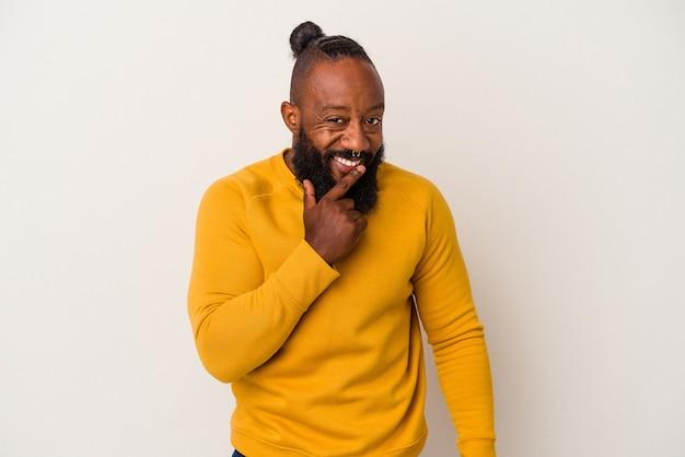 Homem afro-americano com barba isolada na parede rosa, sorrindo feliz e confiante, tocando o queixo com a mão.