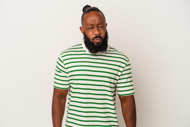 Homem afro-americano com barba isolada no fundo rosa sopra nas bochechas, tem expressão cansada. conceito de expressão facial.