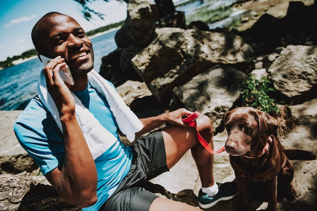 Homem afro-americano com cachorro falando no telefone