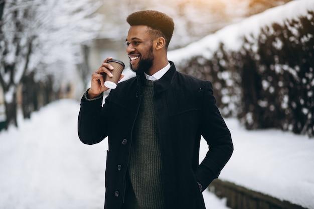Homem afro-americano com café ao ar livre no inverno