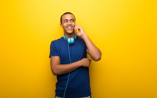 Homem afro-americano com camiseta azul na parede amarela, mantendo uma conversa com o telefone móvel com alguém