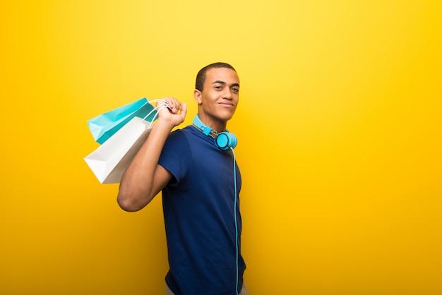 Homem afro-americano com camiseta azul sobre fundo amarelo, segurando um monte de sacolas de compras