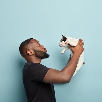 Homem afro-americano com camiseta preta segurando cachorro