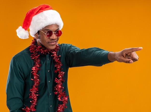 Homem afro-americano com chapéu de papai noel com festão e óculos escuros, olhando para o lado com um sorriso no rosto apontando com o dedo indicador para algo em pé sobre um fundo laranja