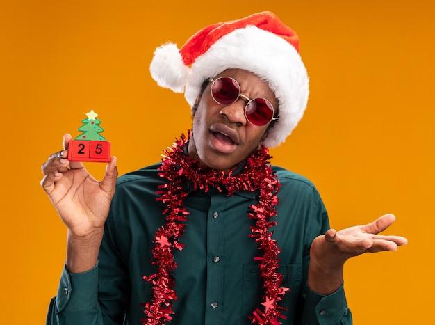 Homem afro-americano com chapéu de papai noel com festão e óculos escuros segurando cubos de brinquedo com data 25, parecendo confuso com o braço estendido em pé sobre um fundo laranja