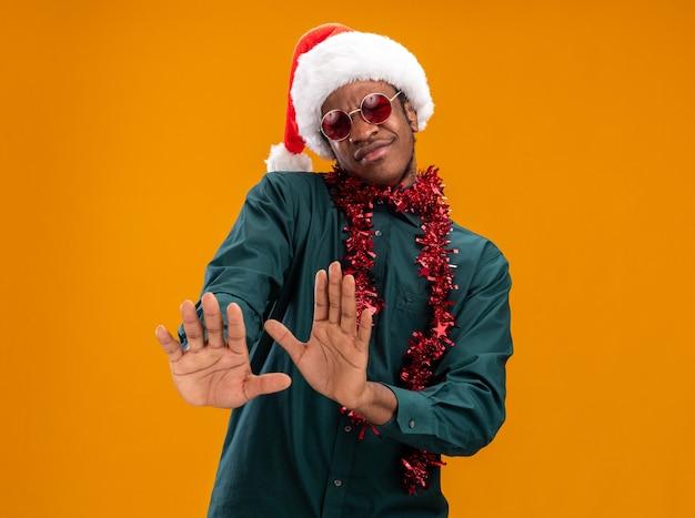 Homem afro-americano com chapéu de papai noel com festão usando óculos escuros, olhando para a câmera, insatisfeito, segurando as mãos, dizendo para não se aproximar em pé sobre um fundo laranja