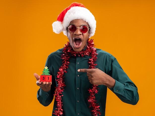 Homem afro-americano com chapéu de papai noel com festão usando óculos escuros segurando cubos de brinquedo com a data de ano novo apontando com o dedo indicador surpreso e espantado em pé sobre um fundo laranja