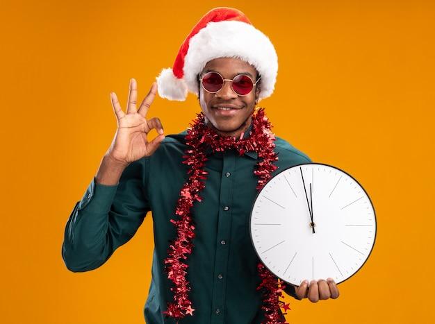 Homem afro-americano com chapéu de papai noel com festão usando óculos escuros, segurando um relógio, olhando para a câmera, sorrindo, mostrando uma placa de ok em pé sobre um fundo laranja