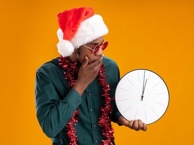 Homem afro-americano com chapéu de papai noel com festão usando óculos escuros segurando um relógio olhando para ele espantado e surpreso em pé sobre um fundo laranja