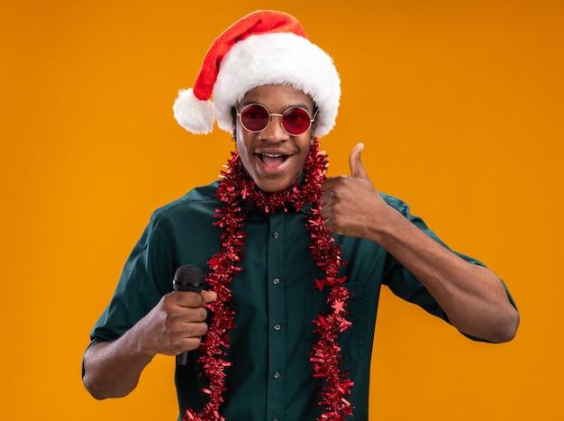 Homem afro-americano com chapéu de papai noel com guirlanda de óculos segurando o microfone e sorrindo mostrando os polegares em pé sobre a parede laranja