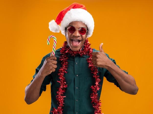 Homem afro-americano com chapéu de papai noel com guirlanda de óculos segurando um bastão de doces e sorrindo mostrando os polegares em pé sobre a parede laranja
