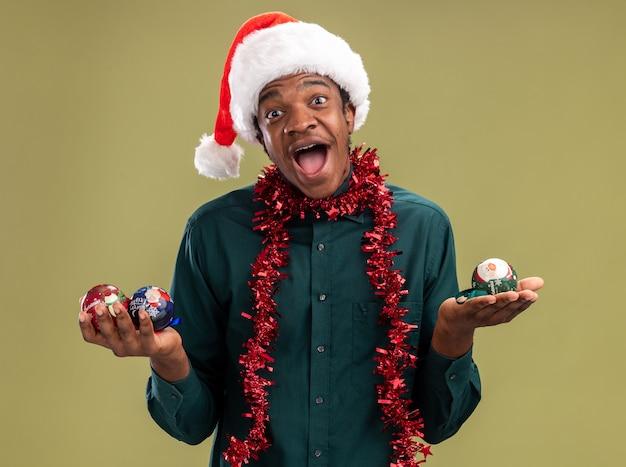 Homem afro-americano com chapéu de papai noel com guirlanda segurando bolas de natal, olhando para a câmera, sorrindo com uma carinha feliz em pé sobre um fundo verde