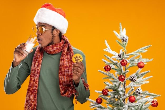 Homem afro-americano com chapéu de papai noel e lenço em volta do pescoço segurando um biscoito, bebendo leite, ao lado de uma árvore de natal sobre fundo laranja