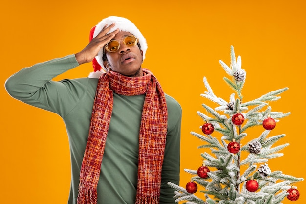 Homem afro-americano com chapéu de papai noel e lenço no pescoço, cansado e entediado, em pé ao lado de uma árvore de natal sobre uma parede laranja