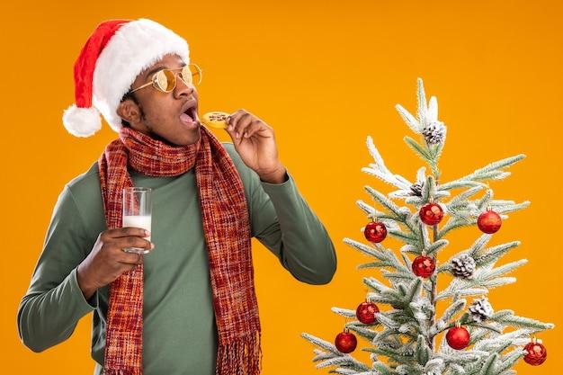 Homem afro-americano com chapéu de papai noel e lenço no pescoço, comendo biscoito, segurando um copo de leite, em pé ao lado de uma árvore de natal sobre fundo laranja