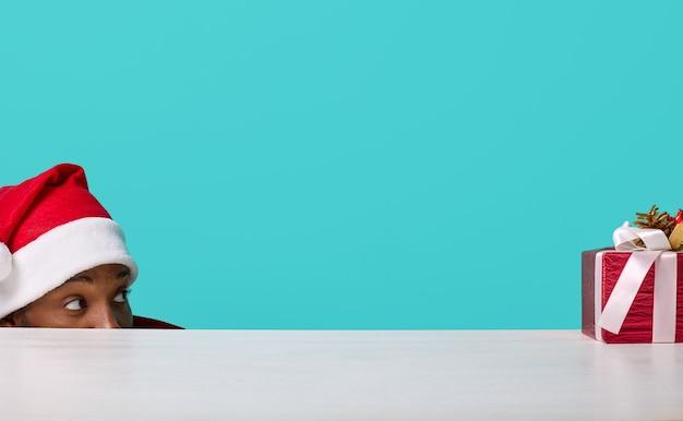 Homem afro-americano com chapéu de papai noel olhando para um presente de natal debaixo da mesa
