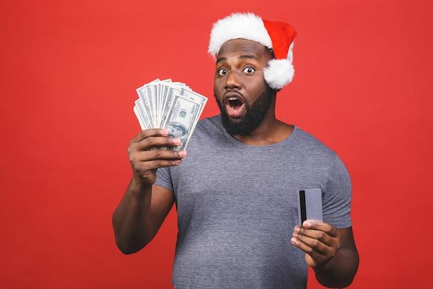 Homem afro-americano com chapéu de papai noel segurando dinheiro e cartão de crédito