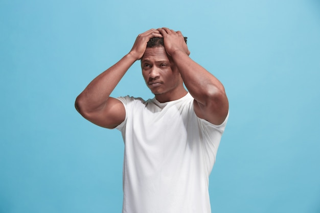 Homem afro-americano com dor de cabeça. isolado sobre a parede azul